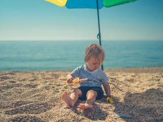 Little toddler sitting under parasol on beach