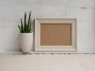 Schlichtes Mockup mit Bilderrahmen und kleiner Pflanze