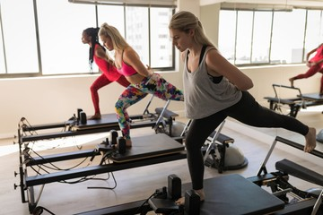 Women exercising on stretching machine in gym