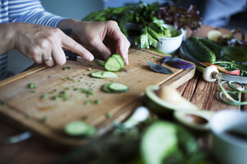 slicing fresh vegetables on wooden cutting board, cooking salad