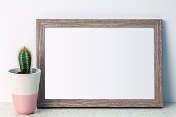 Cactus in a pink patterned pot and wooden copy space frame on a white wall background