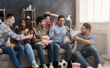 Excited friends watching football match at home
