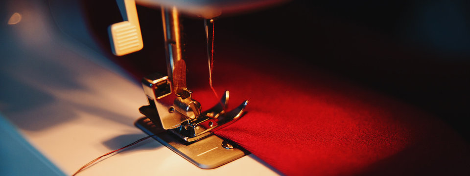 Sewing hobby background. Sewing machine with red fabric. Close up process with copy space. Dramatic dark colors.