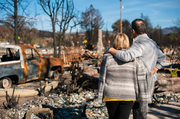 Man and his wife owners, checking burned and ruined of their house and yard after fire, consequences of fire disaster accident. Ruins after fire disaster.