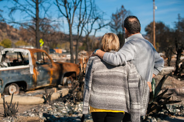 Man and his wife owners, checking burned and ruined of their house and yard after fire, consequences of fire disaster accident. Ruins after fire disaster. Fotomurales