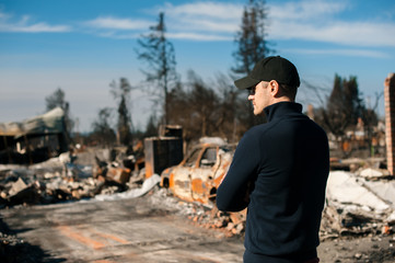 Man owner checking burned and ruined house and yard after fire, consequences of fire disaster accident. Ruins after fire disaster. Fotomurales