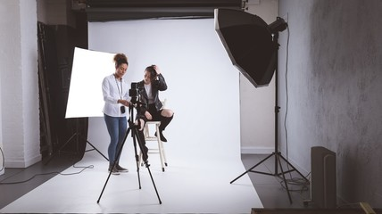 Female photographer and model interacting with each other