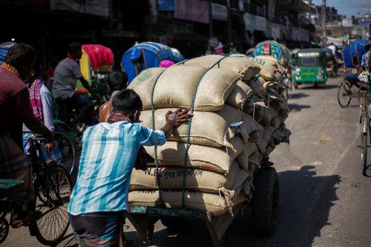 a labor pushing a two wheeler cart full of rice sacks in street of dhaka bangladesh