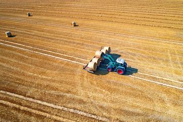 Traktor lädt Strohballen auf einen Anhänger
