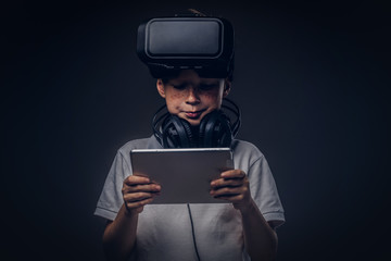 Portrait of a cute little boy dressed in a white t-shirt, with virtual reality glasses and headphones is holding a digital tablet at a studio. Education and technology concept.