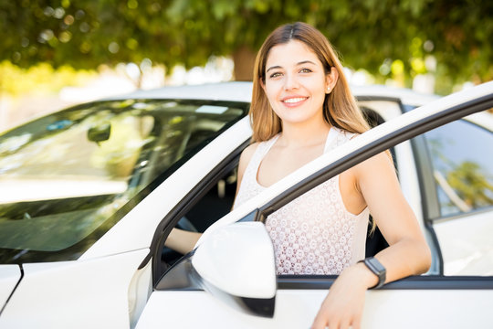 Beautiful woman standing by her car