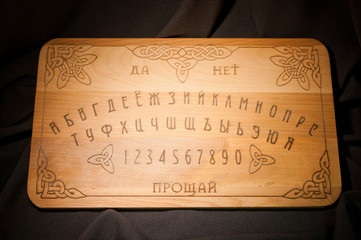 Ouija Board, yellow on a black background