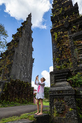 Happy tourist woman is taking a photo with mobile smart phone camera standing near traditional Balinese Hindu gates.