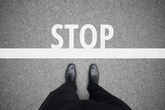 Businessman in black shoes standing at the stop line