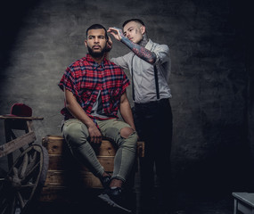 Handsome African American man getting a haircut while sitting on wooden boxes at a studio. Old-fashioned professional hairdresser does a haircut.
