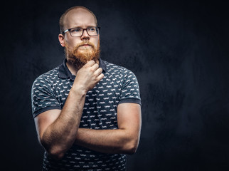 Pensive redhead bearded male in glasses dressed in a t-shirt posing with a hand on chin. Isolated on dark textured background.