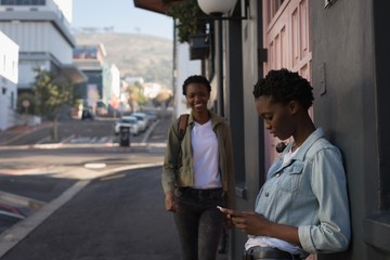 Siblings using smartphone in city street