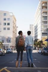 Twins siblings standing in city street