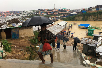 Rohingya refugees walks along the refugee camp during rain in Cox's Bazar