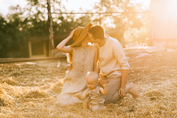 parents with little son in linen clothing near by kissing while resting on hay at countryside