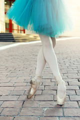 Ballet dancer's feet dancing on street. Young ballerinas in color tutu. Ballet feet on the point.