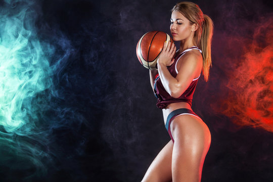 Beautiful and sexy fit woman with a basketball in studio. Sport concept