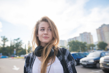 Pretty girl with headphones on her neck stands on the background of the city landscape and looks to the side. Portrait of an attractive girl in casual clothes for a walk.