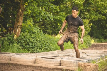 Fit man training over tyres obstacle course