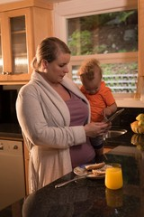 Mother with baby standing in the kitchen and using digital
