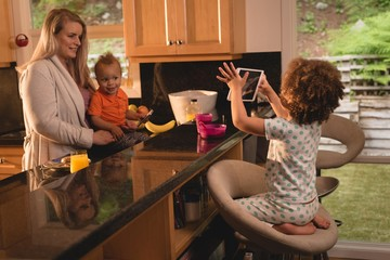 Girl taking photo of mother and baby in the kitchen