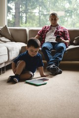 Father and son using digital tablet and mobile phone in living