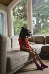 Girl using virtual reality glasses in living room