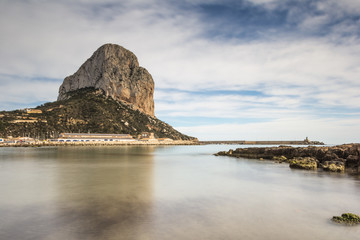Ifach mountain from water in calm and clouds in the blue sky