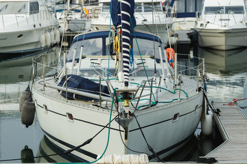 Luxury yachts moored in marina. Boats reflected in the water of Deauville harbor, France. Close up. Yachting, vacation, luxury lifestyle and wealth concept
