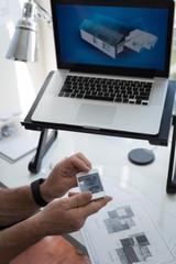 Man using mobile phone while preparing architectural design