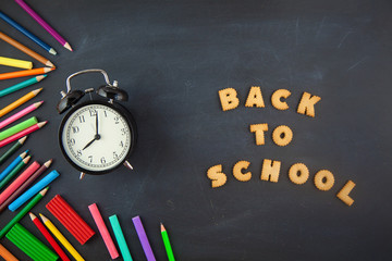 Back to school Accessories for school on a dark background Pencils Plasticine letters Letters Alarm clock Chalk Copy space Top view
