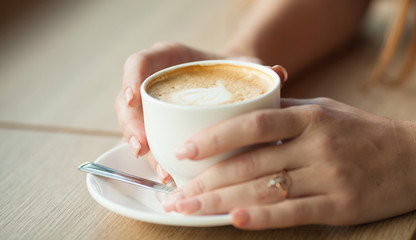 Hand Holding Latte Coffee With Heart Shape