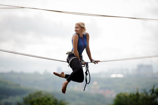 Side view smiling girl sitting on the slackline and looking back