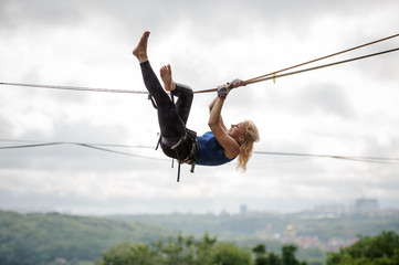 Young woman hanging on the slackline upside down