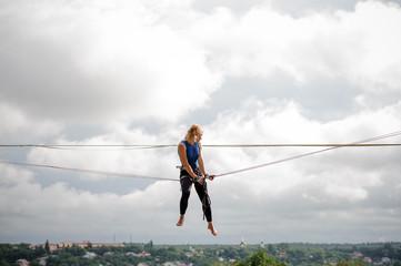 Female equilibrist sitting on the slackline rope