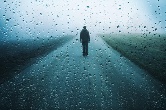 Lonely man stands on misty road with artistic raindrops background.