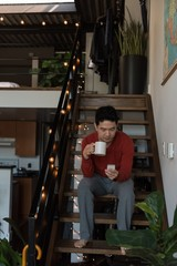 Man having coffee while using mobile phone on stairs