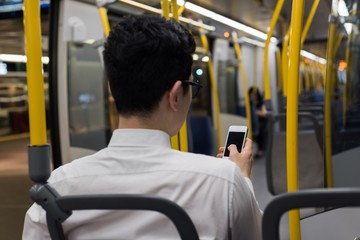 Man using mobile phone while travelling in train