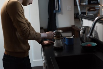 Man preparing black coffee in the kitchen