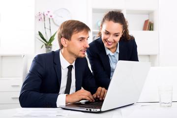 Business male assistant wearing formalwear using laptop