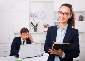 charming young woman manager holding cardboard in office