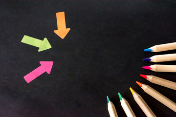Black background flat lay pencils arrows colourful