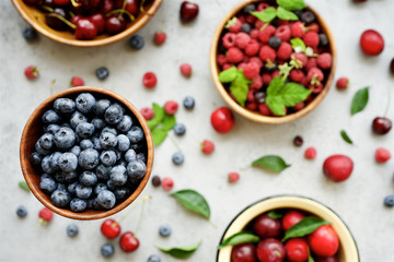 Fresh raspberries, blueberries, plums and cherries in bowls on gray background. Top view