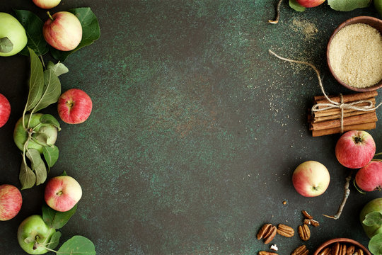 Ripe organic apples with pecans, sugar and cinnamon on dark green background.  Autumn concept