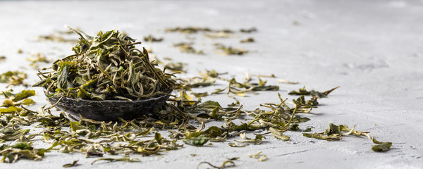 Loose dried white tea leaves on grey background